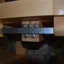 deux rails en aluminium parfaitement parallèles, qui coulissent entre 3+2 roulements, de chaque côté du bloc de bois