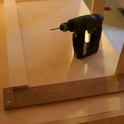 Gabarit de perçage posé en milieu de meuble avec un cale d'alignement